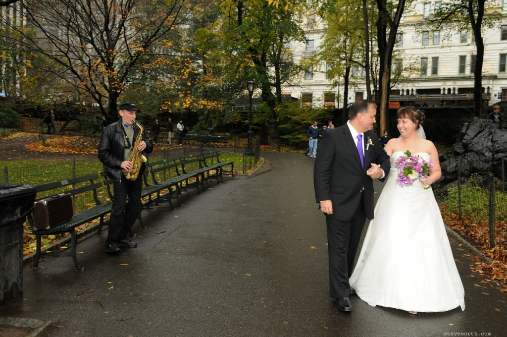 Saxophone player playing for a bride and groom in rainy Central Park